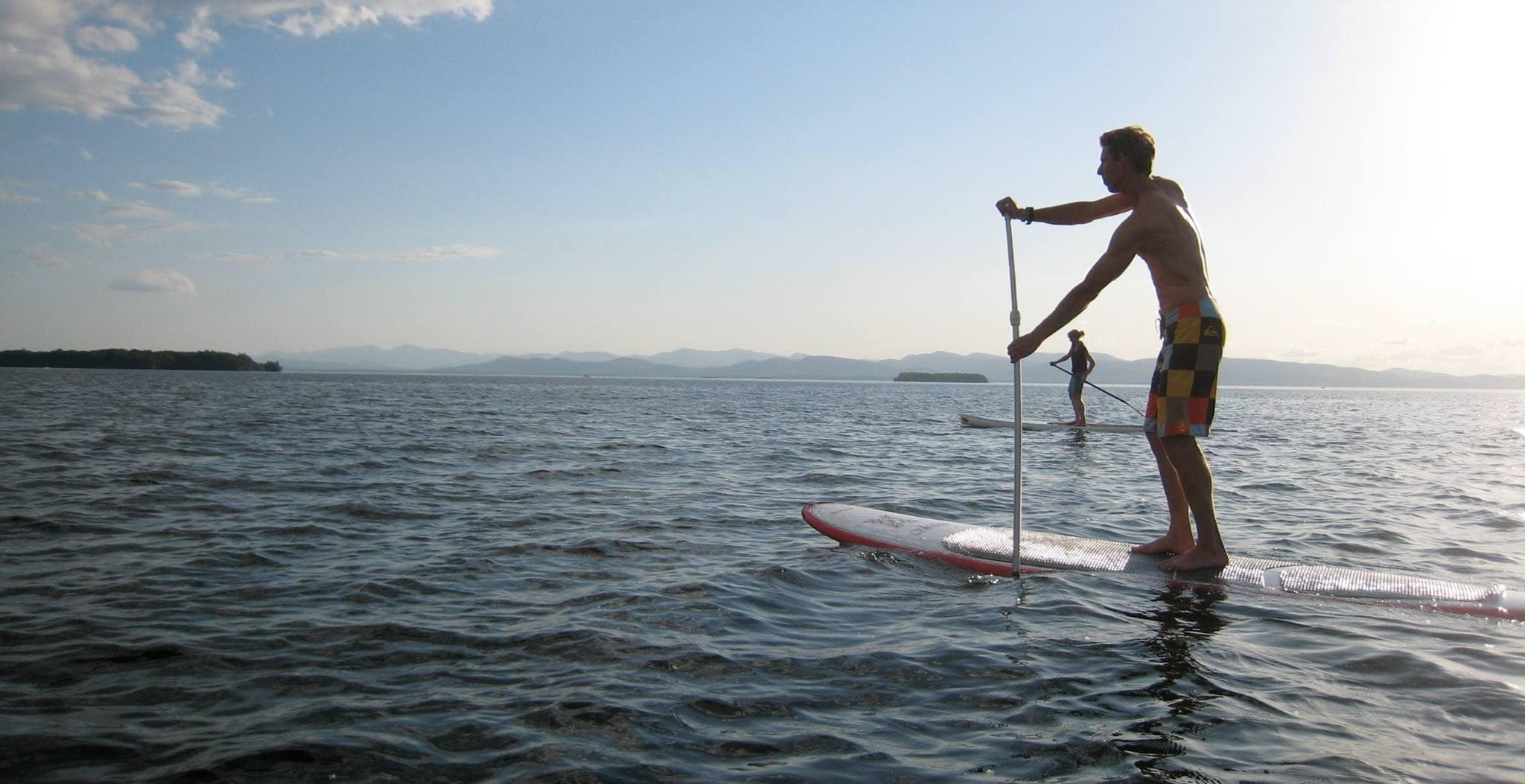 a man paddleboarding on lake champlain